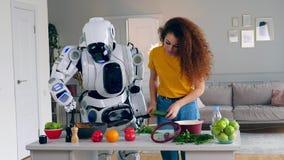 一起年轻女人和靠机械装置维持生命的人厨师晚餐 机器人、靠机械装置维持生命的人和人的概念 股票录像