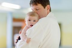 一起年轻父亲和他的小逗人喜爱的新出生的小女儿在温泉旅馆里 库存照片