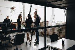 一起年轻队立场和在玻璃墙后谈话在用现代装备的宽敞轻的现代办公室 库存照片