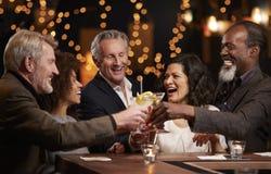 一起庆祝在酒吧的小组中世纪朋友 免版税库存照片