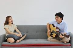 一起弹声学吉他的轻松的年轻亚洲夫妇在客厅 爱和浪漫史人概念 库存照片