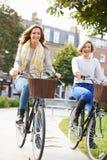 一起循环通过都市公园的两名妇女 免版税库存照片