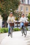 一起循环通过都市公园的两名妇女 库存照片