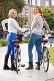 一起循环通过都市公园的两名妇女 库存图片