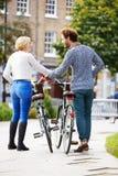 一起循环通过都市公园的夫妇背面图  免版税库存照片