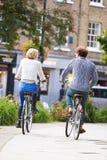 一起循环通过都市公园的夫妇背面图  库存照片