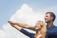 一起微笑在晴天的逗人喜爱的夫妇 免版税库存图片