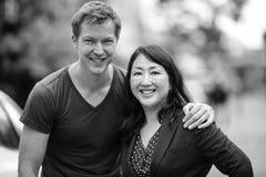 一起成熟美丽的亚裔女实业家和年轻斯堪的纳维亚人在户外街道在黑白 免版税库存照片