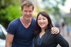 一起成熟美丽的亚裔女实业家和年轻斯堪的纳维亚人在户外街道 免版税库存图片
