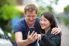 一起成熟美丽的亚裔女实业家和年轻斯堪的纳维亚人在户外街道 库存图片