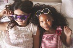 一起戴太阳镜的两个女孩画象在卧室 免版税库存照片