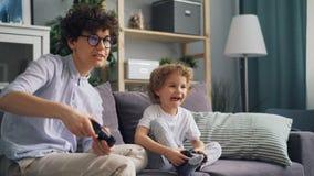 一起打在公寓的幸福家庭母亲和儿子电子游戏获得乐趣 影视素材