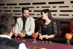 一起打扑克的逗人喜爱的夫妇 免版税图库摄影