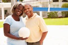 一起打排球的资深夫妇 免版税图库摄影