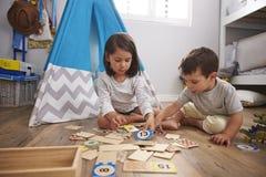 一起打数字难题比赛的两个孩子在游戏室 免版税库存图片