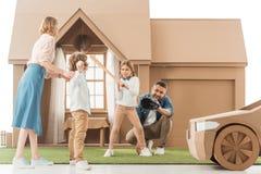 一起打棒球的年轻家庭在围场纸板房子 库存图片