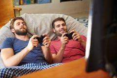 一起打电子游戏的睡衣的两个男性朋友 免版税库存图片