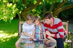 一起打验查员比赛的两个小孩男孩和父亲 图库摄影