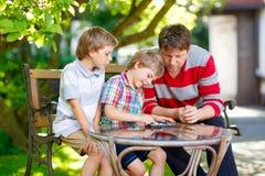 一起打验查员比赛的两个小孩男孩和父亲 库存图片