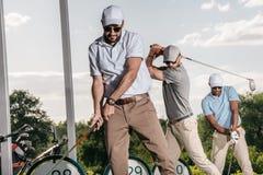 一起打高尔夫球的朋友在高尔夫球场 免版税库存照片
