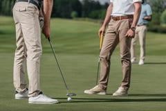 一起打高尔夫球的运动员在高尔夫球场在白天 免版税库存图片
