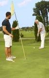 一起打高尔夫球年轻和老的人 库存图片