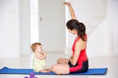一起执行瑜伽的母亲和婴孩 免版税库存照片