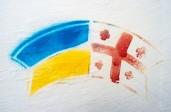 一起拉长的乌克兰和英王乔治一世至三世时期旗子在白色墙壁上在库特 库存照片