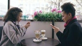 一起拍摄咖啡杯的两个可爱的混合的族种女性朋友使用智能手机照相机,当参加时 股票录像