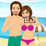 一起拍selfie照片使用智能手机照相机在海滩和显示赞许的年轻夫妇 免版税库存图片