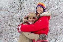 一起拥抱在冬天森林的两个孩子 免版税图库摄影