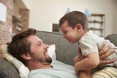 一起拥抱在沙发的父亲和儿子 免版税库存照片