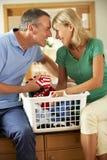 一起排序洗衣店的高级夫妇 免版税库存照片