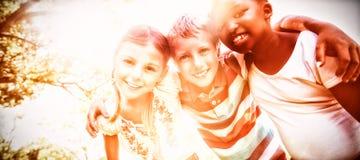 一起摆在一个晴天期间的孩子在照相机 库存照片