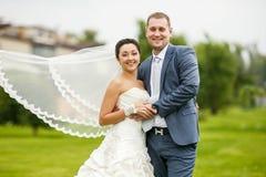 一起摆在室外的新娘和新郎在一婚礼之日 免版税库存图片