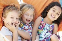 一起放松在庭院吊床的三个孩子 库存照片