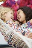 一起放松在庭院吊床的两个女孩 库存图片