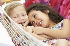 一起放松在庭院吊床的两个女孩 免版税库存图片