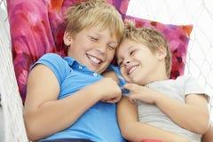 一起放松在庭院吊床的两个年轻男孩 免版税库存图片