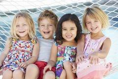 一起放松在庭院吊床的四个孩子 免版税库存图片