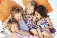 一起放松在庭院吊床的四个孩子 库存图片