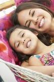 一起放松在庭院吊床的母亲和女儿 免版税库存图片