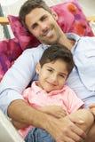 一起放松在庭院吊床的父亲和儿子 免版税库存照片