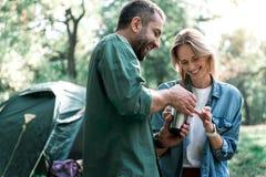 一起放松在森林里的逗人喜爱的爱恋的夫妇 免版税库存图片