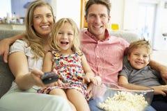 一起放松在沙发观看的电视上的家庭 图库摄影