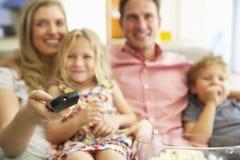 一起放松在沙发观看的电视上的家庭 库存图片