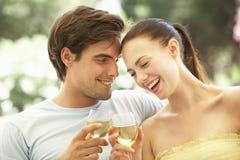 一起放松在沙发饮用的酒的年轻夫妇画象  免版税库存照片