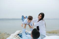 一起放松在湖的愉快的年轻家庭 库存图片