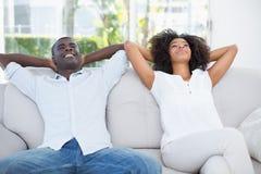 一起放松在长沙发的有吸引力的夫妇 免版税库存照片