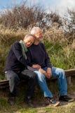 一起放松在阳光下的愉快的资深夫妇 免版税库存图片